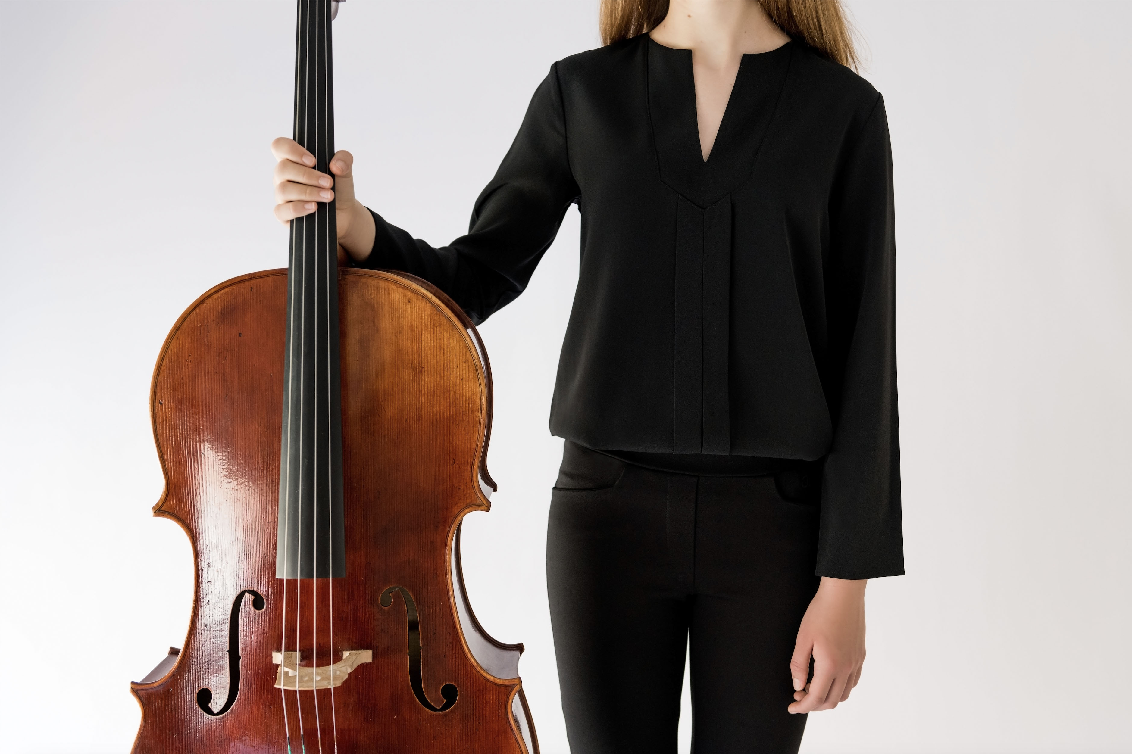 girl dressed in black holding a cello