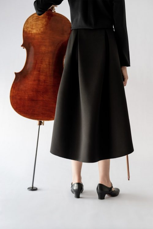 girl standing next to cello wearing black skirt back view