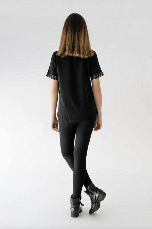 girl standing with black blouse and black pant back view