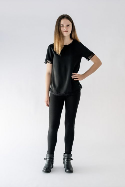 girl standing black blouse black pant front view