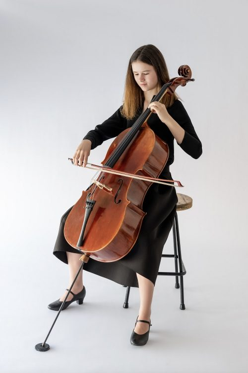 girl sitting playing cello