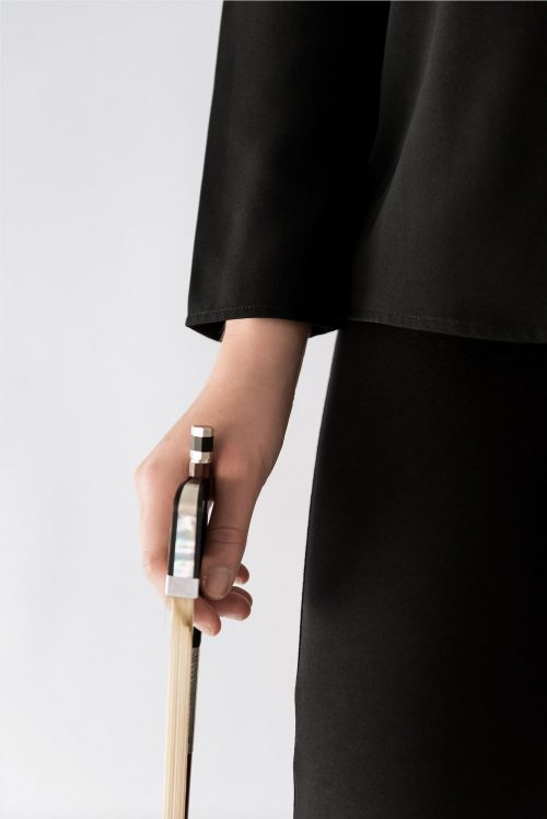 hand holding cello bow with long sleeve