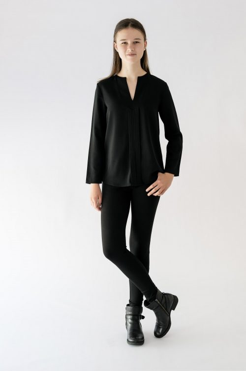 girl standing wearing black blouse and black pant