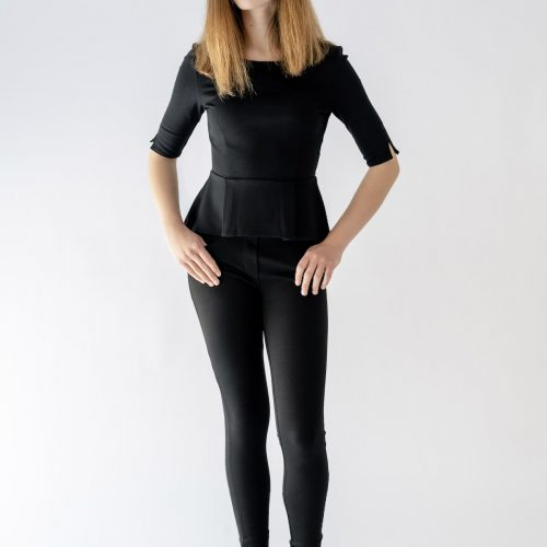 girl standing wearing black pant and peplum top