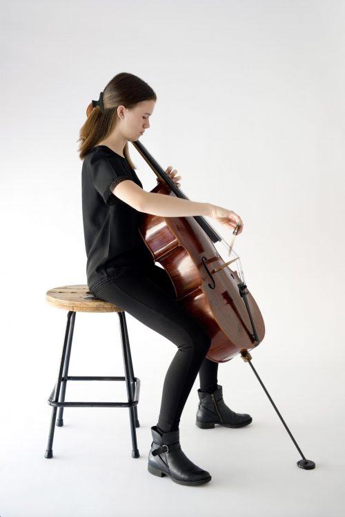 girl sitting playing cello in concert blacks