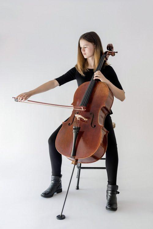 girl sitting playing cello
