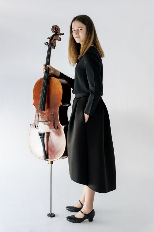 girl standing holding cello