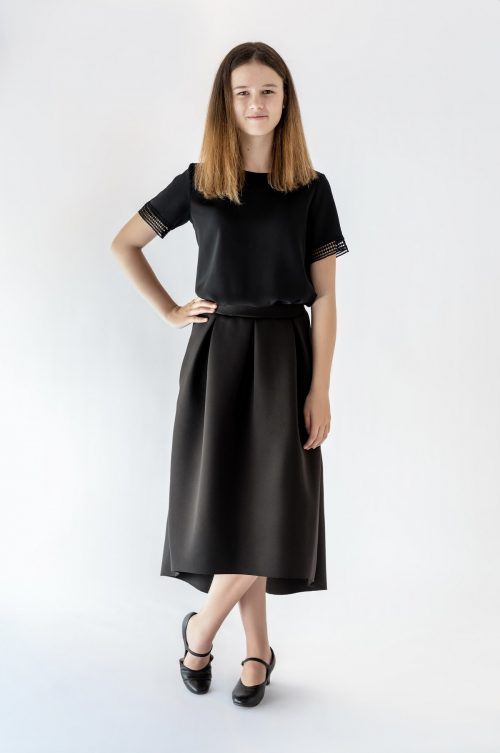 girl standing wearing black skirt and black blouse