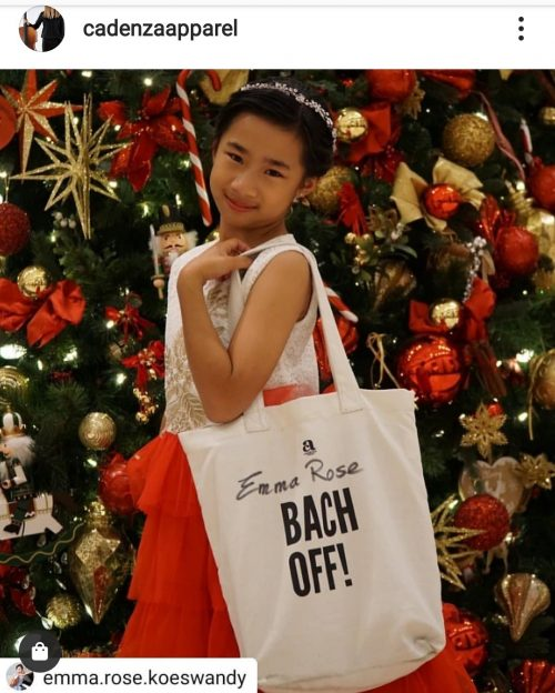 girl with bach off tote bag in front of christmas tree