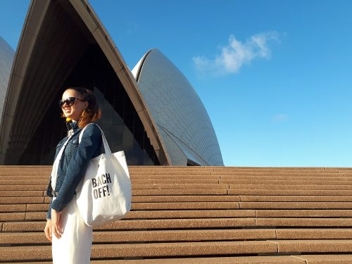 girl standing in front of opera house holding a bag