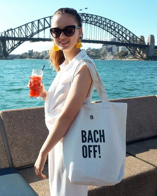 girl with bach off tote bag in front of sydney harbour bridge