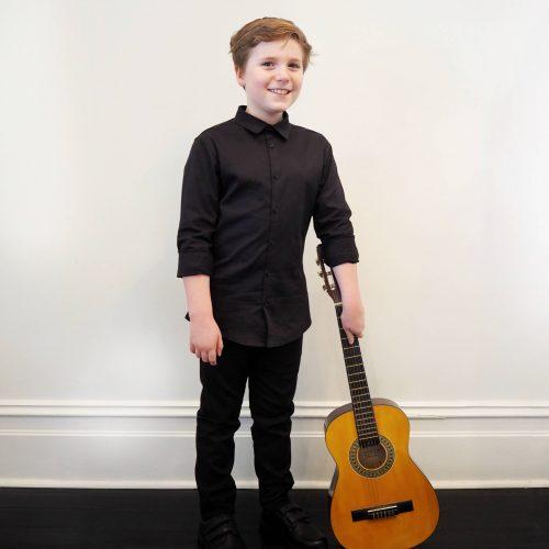 boy posing with guitar wearing black buttoned shirt