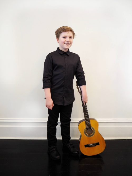 boy posing with guitar wearing black buttoned shirt