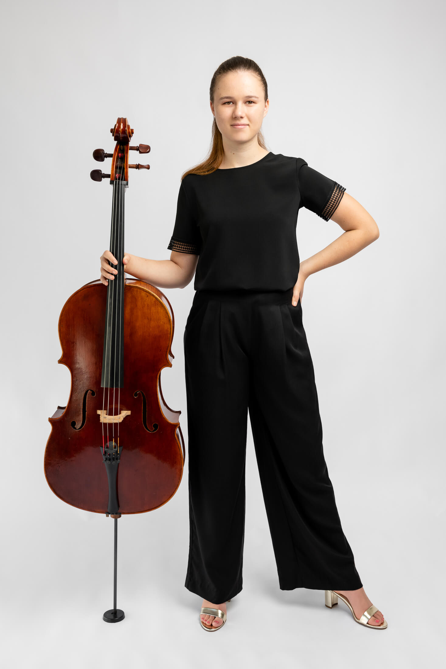 girl in black clothes holding cello